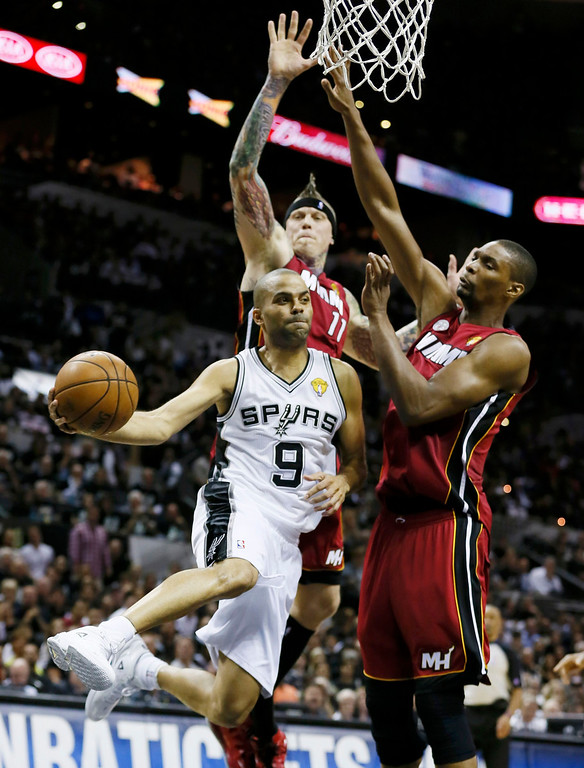 . San Antonio Spurs\' Tony Parker (9) passes off while being guarded by Miami Heat\'s Chris Andersen (11) and Chris Bosh (R) in the first half during Game 3 of their NBA Finals basketball series in San Antonio, Texas June 11, 2013.  REUTERS/Lucy Nicholson
