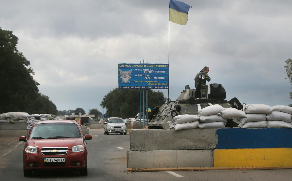 """. Ukrainian forces guard  a checkpoint in the town of Mariupol, eastern Ukraine, Thursday, Aug. 28, 2014. Ukraine\'s president Petro Poroshenko called an emergency meeting of the nation\'s security council and canceled a foreign trip Thursday, declaring that \""""Russian forces have entered Ukraine,\"""" as concerns grew about the opening of a new front in the conflict. (AP Photo/Sergei Grits)"""