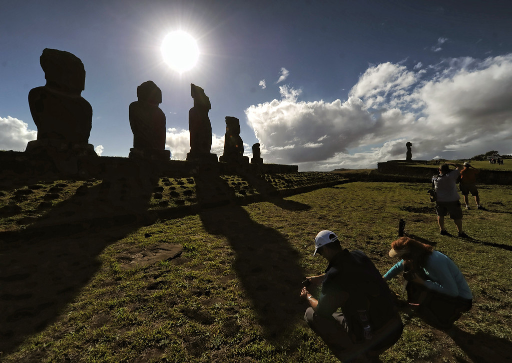. A group of tourists visit Moais (backgorund) -- stone statues of the Rapa Nui culture -- on Easter Island, 3700 km off the Chilean coast in the Pacific Ocean, on July 9, 2010.  MARTIN BERNETTI/AFP/Getty Images