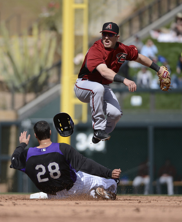 . SCOTTSDALE, AZ. - FEBRUARY 24: Cliff Pennington (4) of the Arizon Diamondbacks sails over a sliding Nolan Arenado (28) of the Colorado Rockies to complete the double play during their game February 24, 2013 in Scottsdale. (Photo By John Leyba/The Denver Post)