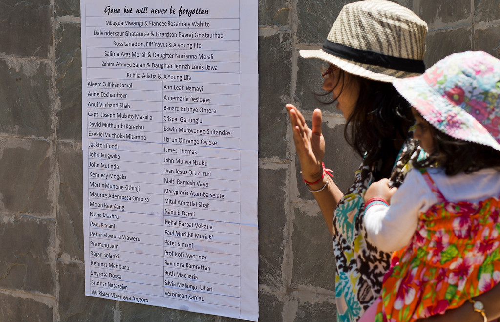 . Relatives of Westgate attack victim Mitul Shah observe a list of names of some of those who died, at a memorial service marking the one-month anniversary of the Sept. 21 Westgate Mall terrorist attack, in Karura Forest in Nairobi, Kenya Monday, Oct. 21, 2013. (AP Photo/Ben Curtis)