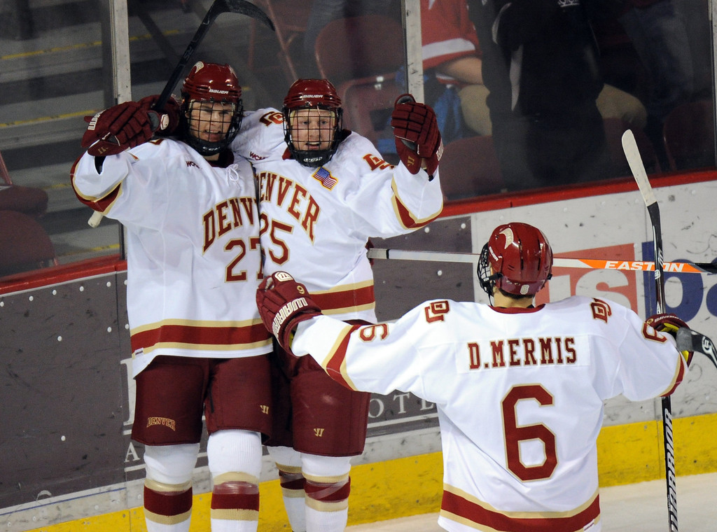 . From left, University of Denver Quentin Shore, Matt Tabrum and Dakota Mermis celebrate a goal by Shore on Boston University goalie Matt O\'Connor in the 1st period of the game at Magness Arena on in Denver on Saturday, Dec. 29, 2012. Hyoung Chang, The Denver Post