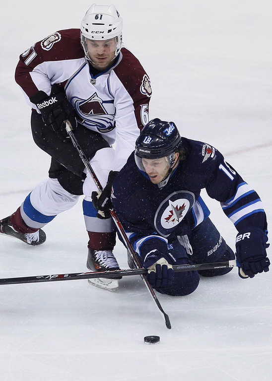 . Colorado Avalanche\'s Andre Benoit (61) and Winnipeg Jets\' Bryan Little (18) scramble for possession of the puck during the first period of an NHL hockey game Wednesday, March 19, 2014, in Winnipeg, Manitoba. (AP Photo/The Canadian Press, John Woods)