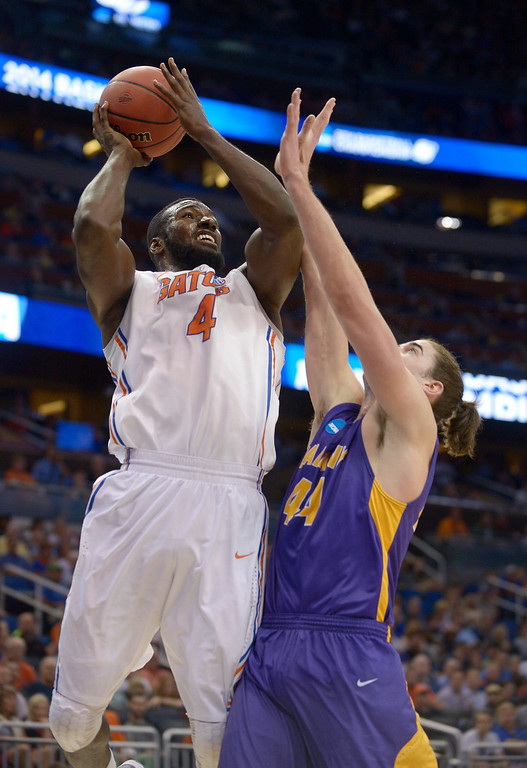 . Florida center Patric Young (4) drives to the basket over Albany center John Puk (44) during the first half of a second-round game in the NCAA college basketball tournament on Thursday, March 20, 2014, in Orlando, Fla. (AP Photo/Phelan M. Ebenhack)