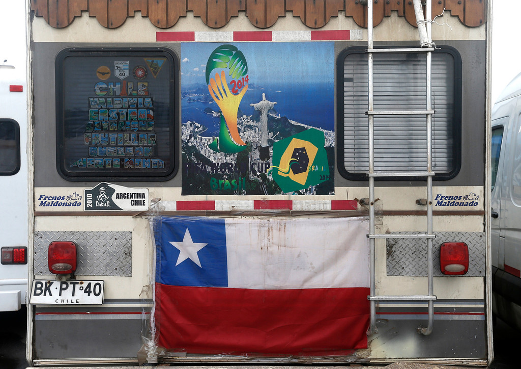 . A motorhome decorated with a Chilean flag and World Cup poster showing a photo of Christ the Redeemer sits parked in the Terreirao do Samba area of Rio de Janeiro, Brazil, Saturday, June 21, 2014. Some soccer fans who came for the World Cup in recreational vehicles were relocated from Copacabana beach to this area designed for events during carnival. (AP Photo/Silvia Izquierdo)