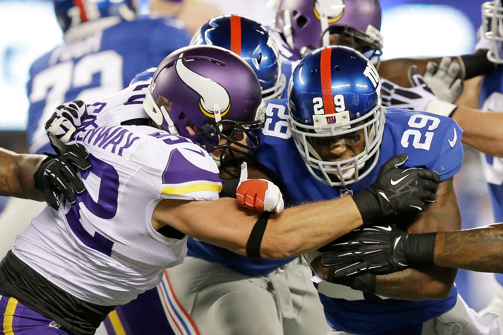 . Minnesota Vikings outside linebacker Chad Greenway, left, tackles New York Giants running back Michael Cox (29) during the first half of an NFL football game Monday, Oct. 21, 2013 in East Rutherford, N.J. (AP Photo/Julio Cortez)