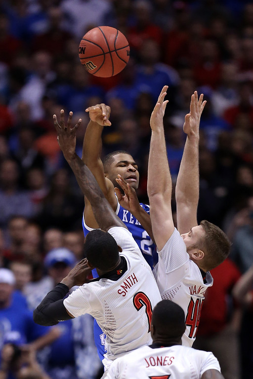 . Aaron Harrison #2 of the Kentucky Wildcats passes the ball over Russ Smith #2 and Stephan Van Treese #44 of the Louisville Cardinals during the regional semifinal of the 2014 NCAA Men\'s Basketball Tournament at Lucas Oil Stadium on March 28, 2014 in Indianapolis, Indiana.  (Photo by Jonathan Daniel/Getty Images)