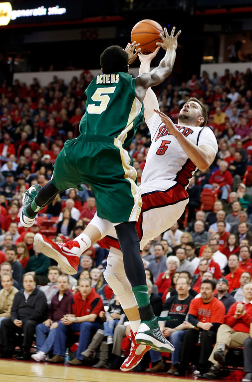 . UNLV\'s Katin Reinhardt, right, shoots guarded by Colorado State\'s Jonathan Octeus during the second half of an NCAA college basketball game on Wednesday, Feb. 20, 2013, in Las Vegas. UNLV defeated Colorado State 61-59. (AP Photo/Isaac Brekken)