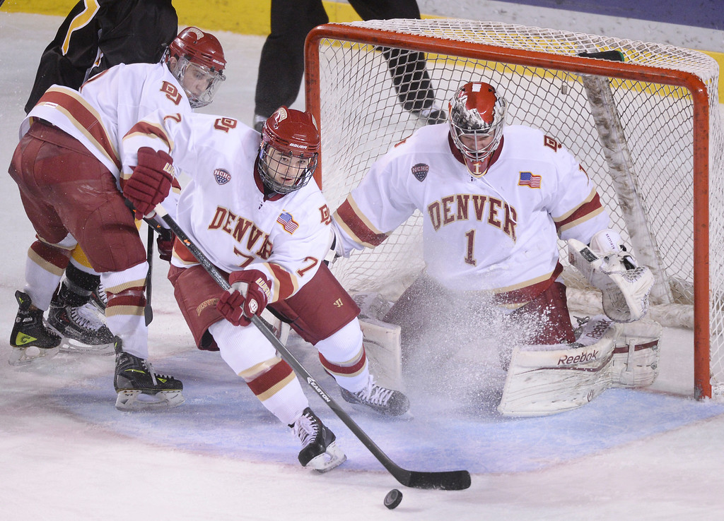 . DENVER, CO. - FEBRUARY 21, 2014: Denver defenseman Will Butcher cleared the puck in the third period. The Colorado College hockey team defeated Denver 3-2 at Magness Arena Friday night, February 21, 2014. Photo By Karl Gehring/The Denver Post