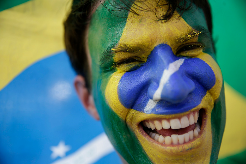 . A soccer fan with his face painted to represent Brazil\'s national flag, poses for a photo as he waits to enter the Arena Castelao, for the World Cup quarterfinal match between Brazil and Colombia, in Fortaleza, Brazil, Friday, July 4, 2014. (AP Photo/Felipe Dana)