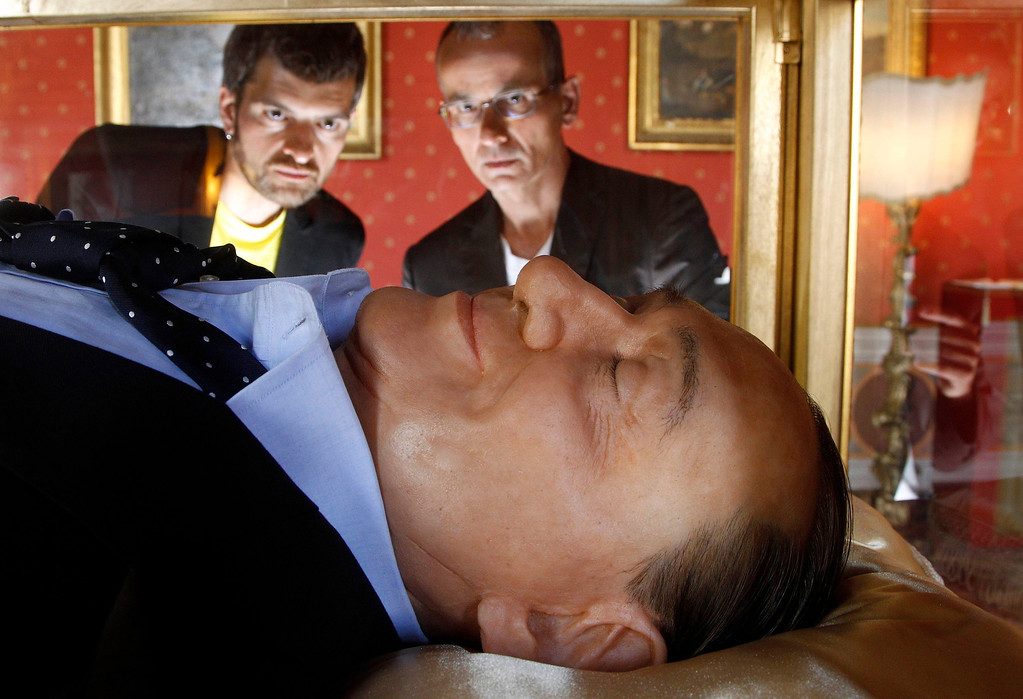 """. Italian artists Antonio Garullo (R) and Mario Ottocento (L) look at their exhibit entitled \""""The Dream Of Italian\"""", which comprises of a wax figurine representing Italy\'s former prime minister Silvio Berlusconi as being dead, at the Ferrajoli Palace in downtown Rome May 29, 2012. REUTERS/Alessandro Bianchi"""