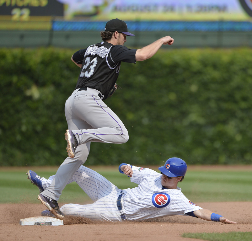 . Shortstop Charlie Culberson #23 of the Colorado Rockies (L) turns a double play after forcing out Chris Coghlan #8 of the Chicago Cubs at second base on a ground ball hit by Starlin Castro during the eighth inning at Wrigley Field on July 31, 2014 in Chicago, Illinois.  (Photo by Brian Kersey/Getty Images)