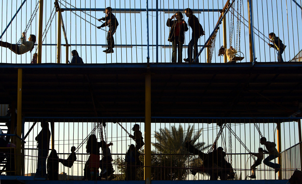 . Iraqis enjoy an amusement park as they celebrate the last day of the Eid al-Adha holiday February 4, 2004 in Baghdad, Iraq. The Muslim holiday of Eid al-Adha (Festival of Sacrifice), takes place on the tenth day of the Islamic month Dhul-Hijjah, the last month of the Islamic calendar in which millions of Muslims from around the world make an annual pilgrimage to Makkah in order to worship Allah and to commemorate the willingness of the Prophet Abraham to sacrifice his son, Ishmael. (Photo by Mario Tama/Getty Images)