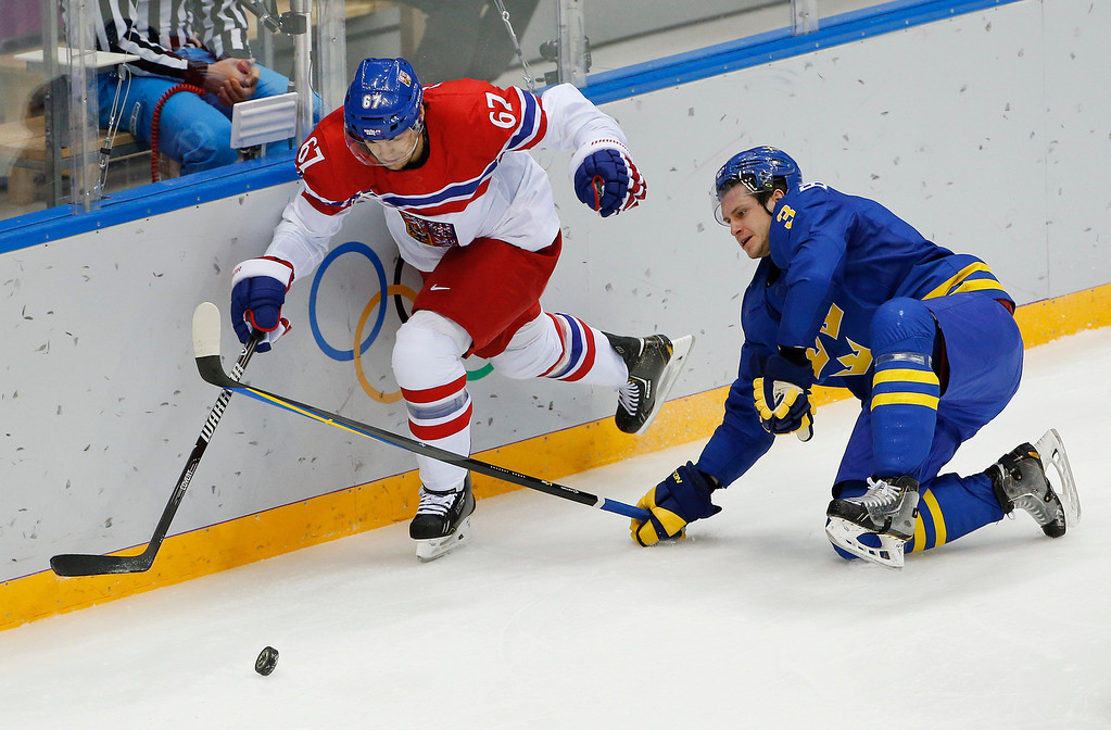 . Czech Republic forward Michael Frolik and Sweden defenseman Oliver Ekman-Larsson vie for the puck in the third period of a men\'s ice hockey game at the 2014 Winter Olympics, Wednesday, Feb. 12, 2014, in Sochi, Russia. (AP Photo/Julio Cortez)