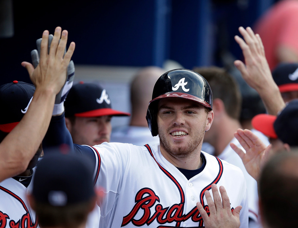 . Atlanta Braves\' Freddie Freeman celebrates in the dugout after hitting a solo home run in the first inning of a baseball game against the Colorado Rockies in Atlanta, Tuesday, July 30, 2013. (AP Photo/John Bazemore)