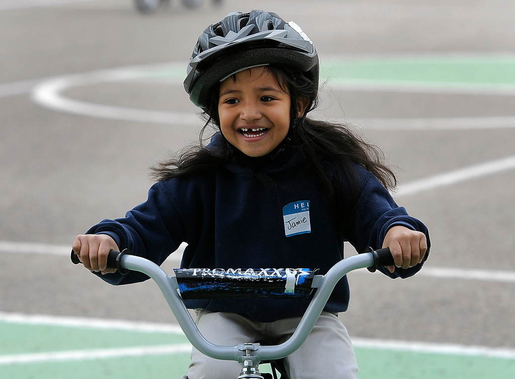 . DENVER, CO - Oct. 11: Jamie Correa, 6, joins her classmates for a spin on the school blacktop. Wish for Wheels and its volunteers build and give away over one hundred bikes to kindergarteners and first-graders at Smith Renaissance School in Park Hill. Wish for Wheels says its goal with one-in-five children liven in poverty, is to give as many kids as possible their first brand new bike and helmet. (Photo By Kathryn Scott Osler/The Denver Post)