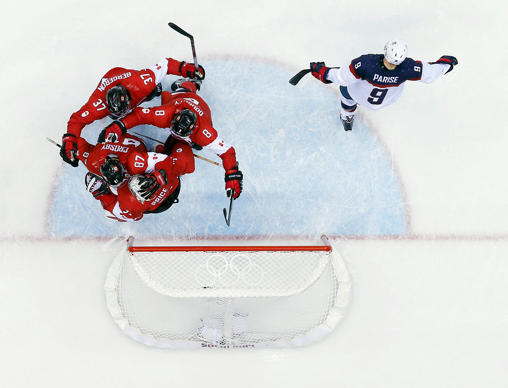. USA forward Zach Parise skates off the ice as Canadian players celebrate after a men\'s semifinal ice hockey game at the 2014 Winter Olympics, Friday, Feb. 21, 2014, in Sochi, Russia. Canada won 1-0 to advance to the gold medal game. (AP Photo/David J. Phillip )