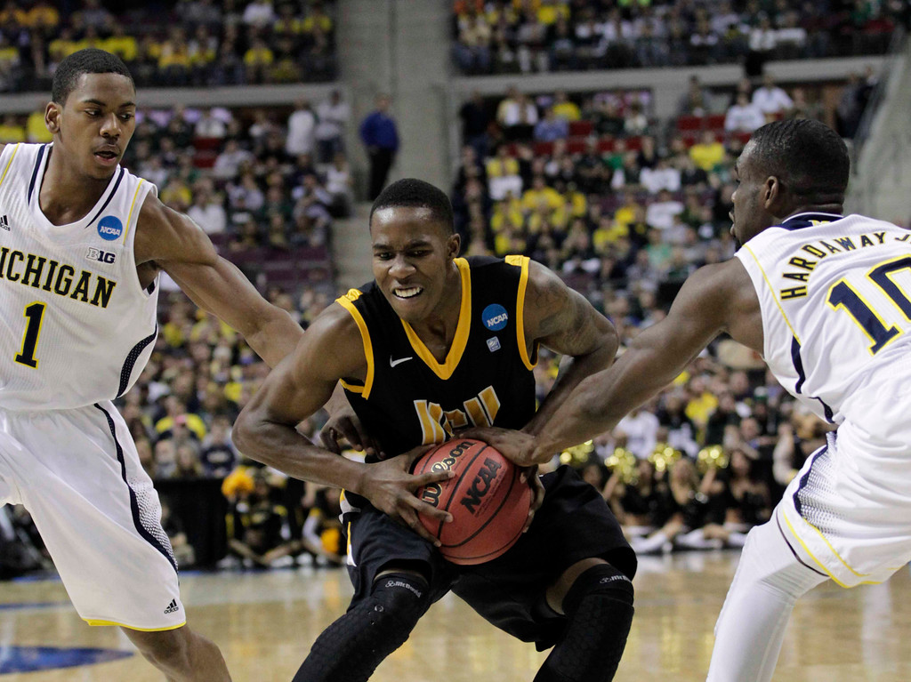 . VCU Rams\' Rob Brandenberg is defended by Michigan Wolverines\' Glenn Robinson III (L) and Tim Hardaway Jr. (R) during the first half of their third round NCAA tournament basketball game in Auburn Hills, Michigan March 23, 2013.  REUTERS/ Jeff Kowalsky