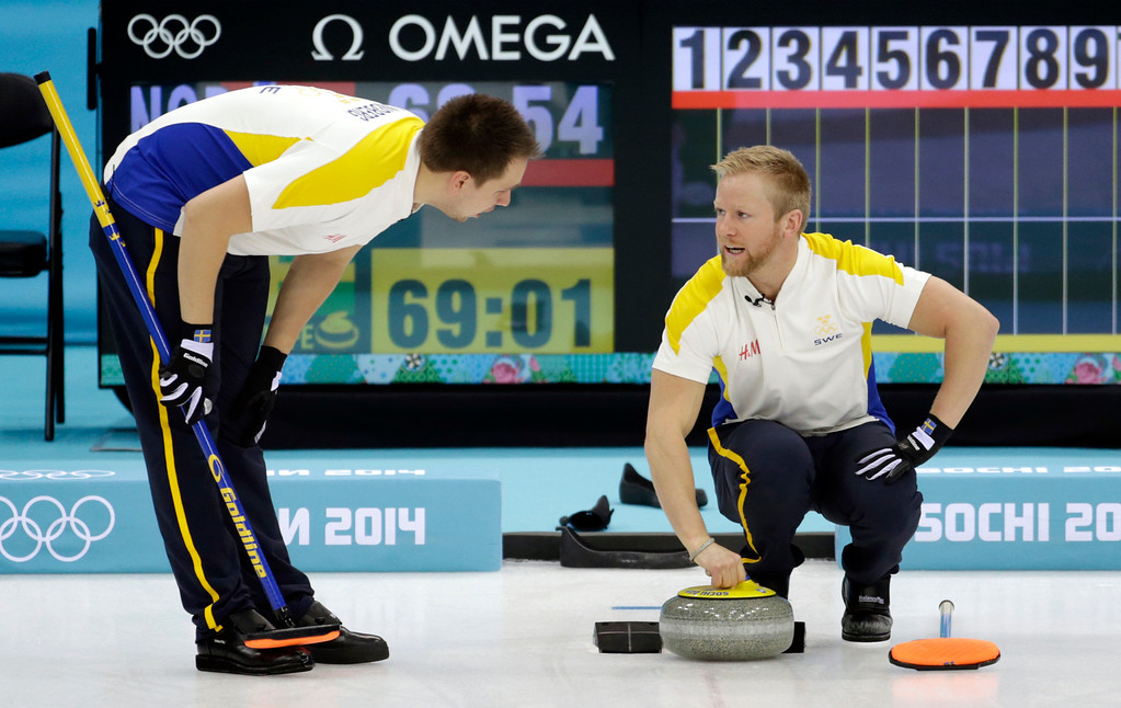 . Swedenís Fredrik Lindberg, left, talks with skip Niklas Edin at the start of men\'s curling competition against Norway at the 2014 Winter Olympics, Thursday, Feb. 13, 2014, in Sochi, Russia. (AP Photo/Robert F. Bukaty)