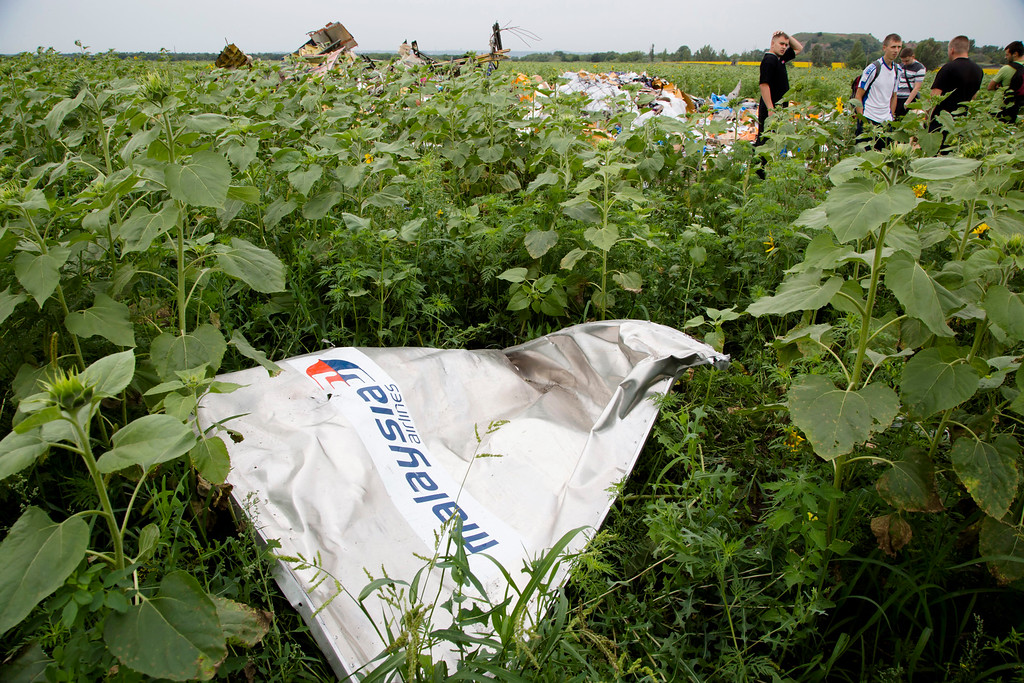 ". A piece of a plane with the sign ""Malaysia Airlines\"" lies in the grass as a group of Ukrainian coal miners search the site of a crashed Malaysian passenger plane near the village of Rozsypne, Ukraine, eastern Ukraine Friday, July 18, 2014. Rescue workers, policemen and even off-duty coal miners were combing a sprawling area in eastern Ukraine near the Russian border where the Malaysian plane ended up in burning pieces Thursday, killing all 298 aboard. (AP Photo/Dmitry Lovetsky)"