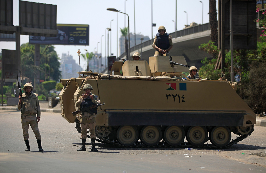 . Egyptian army soldiers stand guard with their weapons at an entrance to Sphinx Square in Cairo, Egypt, Friday, Aug. 30, 2013. Several thousand people heeded calls by the Muslim Brotherhood and protested Friday throughout Cairo and other cities against a coup and deadly crackdown as the police and army blocked key roads and beefed up security.(AP Photo/Khalil Hamra)