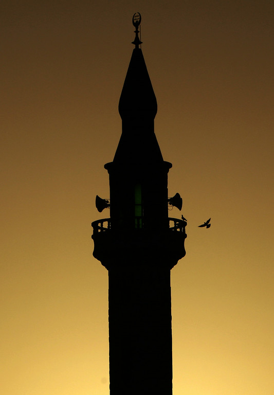 . A bird flies towards the minaret of a mosque in the West Bank refugee camp of Jenin on Saturday, June 28, 2014. Muslims throughout the world are preparing themselves for the holy month of Ramadan, when the observant fast from dawn till dusk. (AP Photo/Mohammed Ballas)