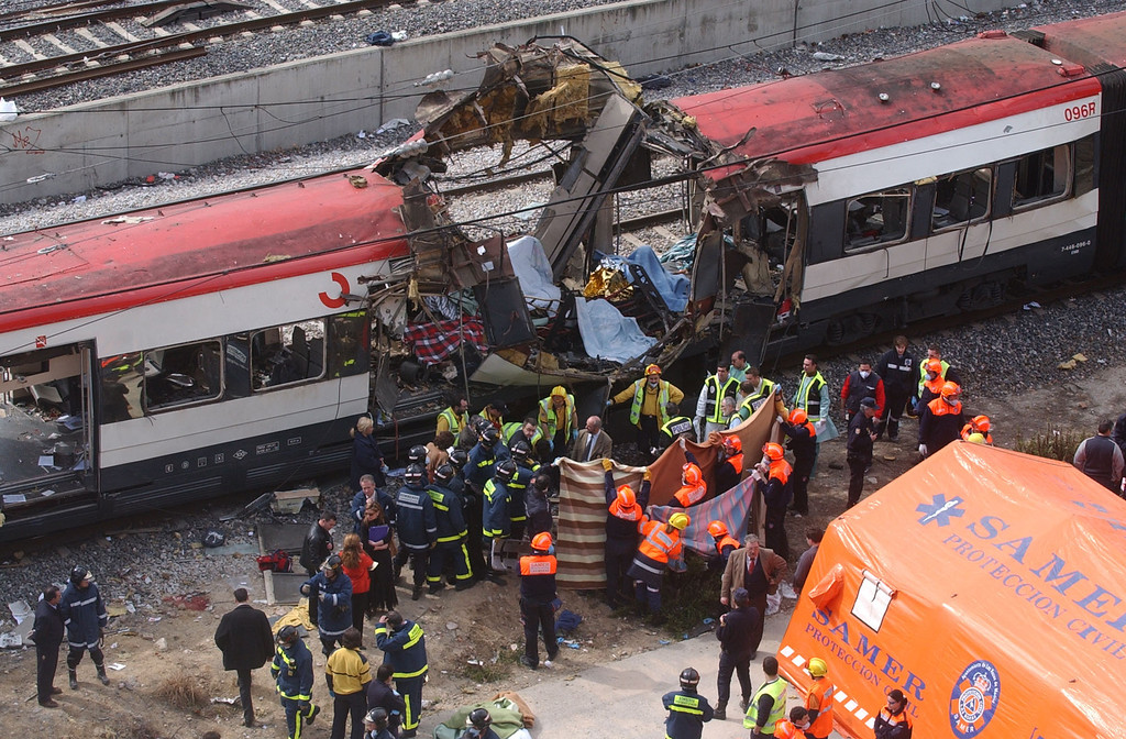 . Rescue workers cover up bodies by a bomb damaged passenger train following a number of explosions on trains in Madrid, Spain, March 11, 2004, just three days before Spain\'s general elections, killing more than 170 rush-hour commuters and wounding more than 500 in Spain\'s worst terrorist attack ever. (AP Photo/Paul White)