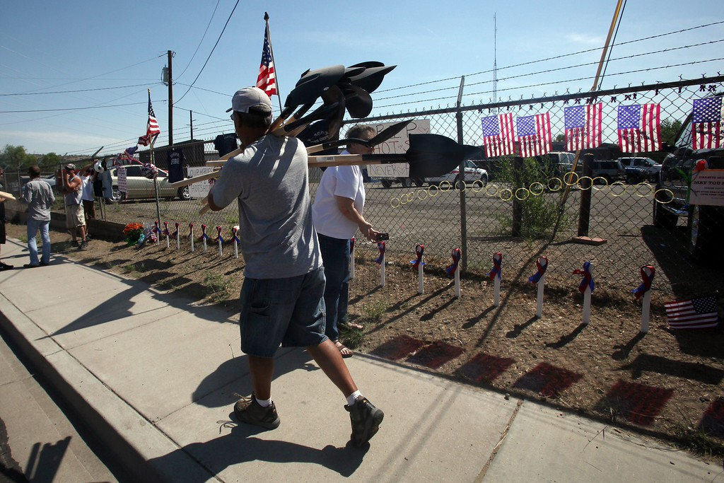 . Anthony Delgrolice carries shovels to place at a memorial outside of Granite Mountain Hotshots Fire Station 7 in Prescott, Arizona July 2, 2013.  AFP PHOTO / KRISTA  Kennell/AFP/Getty Images