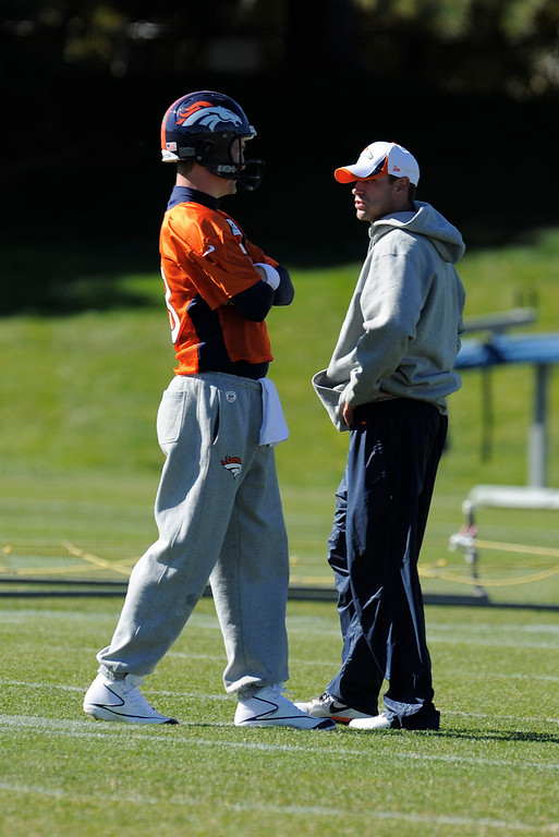 . Denver Broncos quarterback Peyton Manning (18) talks with Adam Gase during practice October 23, 2013 at Dove Valley. Manning talks with Gase while the quarterbacks threw. Peyton did not participate. (Photo by John Leyba/The Denver Post)