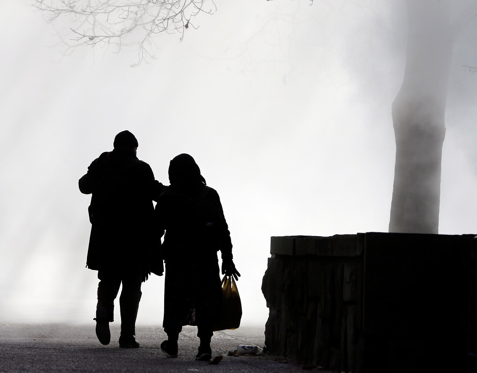 . Pedestrians walk through a cloud of steam being released from a state agency building at the Empire State Plaza on a frigid winter morning on Wednesday, Jan. 22, 2014, in Albany, N.Y.  A winter storm stretched from Kentucky to New England but hit hardest along the heavily populated Interstate 95 corridor between Philadelphia and Boston. (AP Photo/Mike Groll)