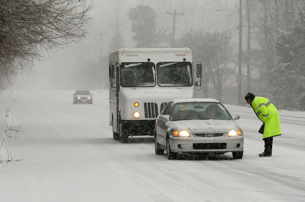 . A police officer redirects traffic as a winter storm moves into the area Wednesday, Feb. 12, 2014, in Charlotte, N.C. (AP Photo/Chuck Burton)