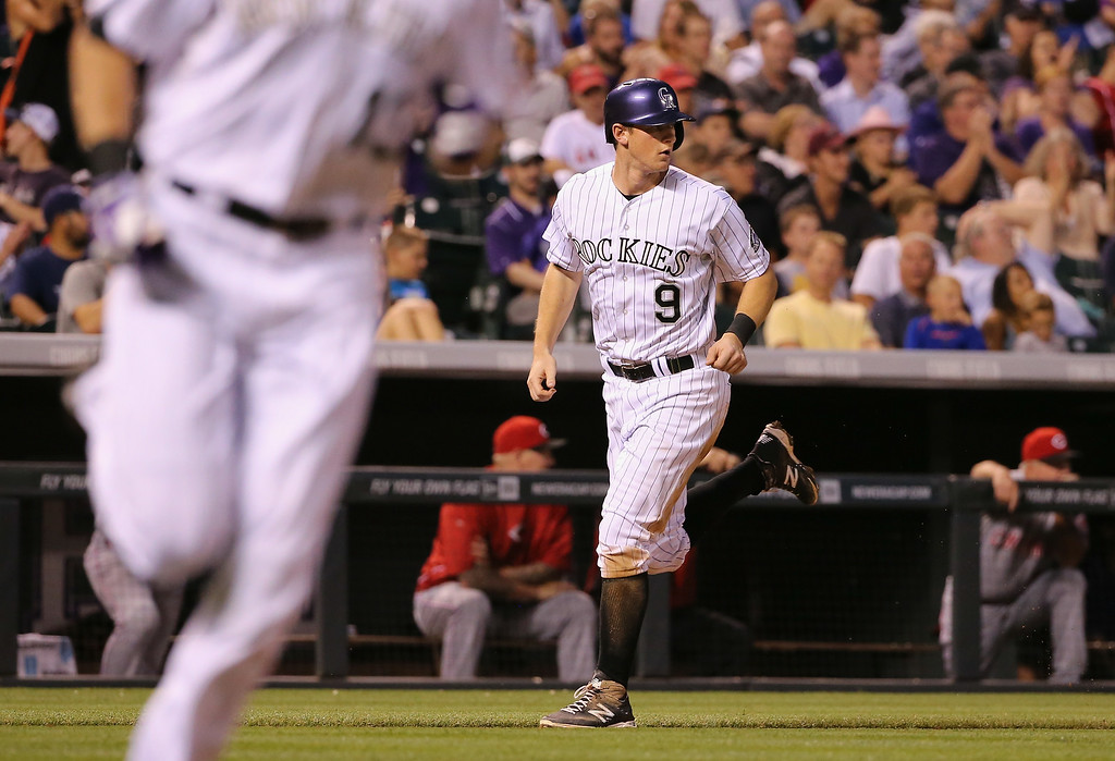 . DENVER, CO - AUGUST 14:  DJ LeMahieu #9 of the Colorado Rockies scores on an RBI single by Drew Stubbs #13 of the Colorado Rockies to take a 4-2 lead over the Cincinnati Reds in the fourth inning at Coors Field on August 14, 2014 in Denver, Colorado.  (Photo by Doug Pensinger/Getty Images)