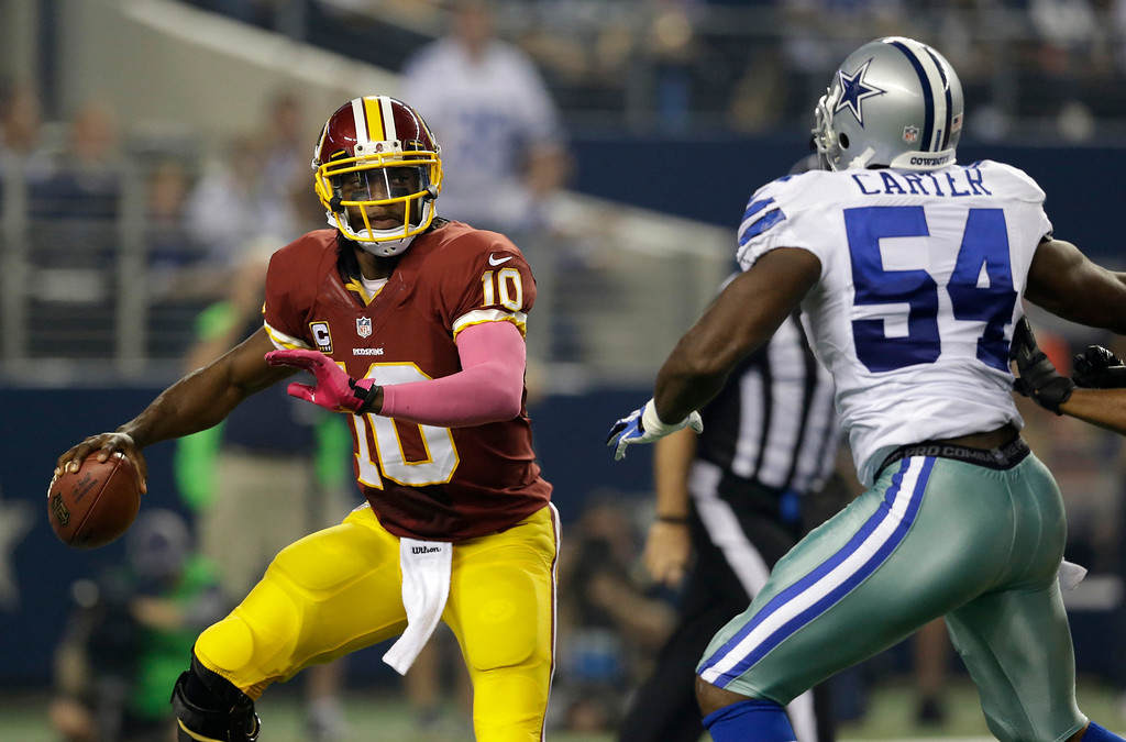 . Washington Redskins quarterback Robert Griffin III (10) scrambles out of the pocket as Dallas Cowboys outside linebacker Bruce Carter (54) defends in the first half of an NFL football game, Sunday, Oct. 13, 2013, in Arlington, Texas. (AP Photo/LM Otero)