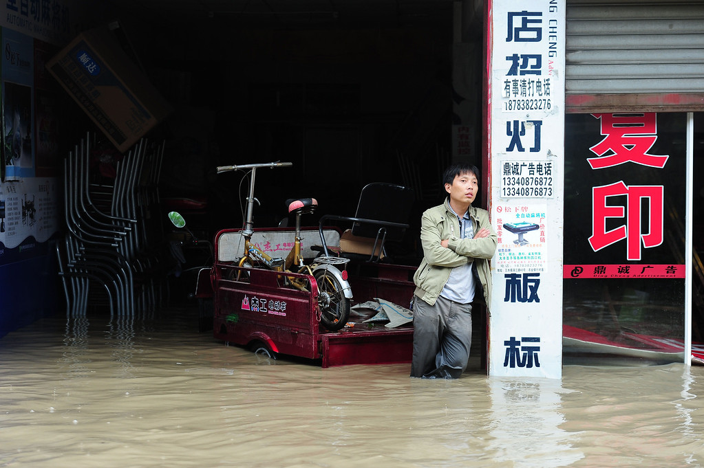 . A man stands in his flooded shop in in Guanghan, southwest China\'s Sichuan province. Rainstorms sweeping across parts of China have affected millions, causing landslides and disabling transportation in provinces such as Sichuan and Yunnan, state media reported.   AFP/Getty Images