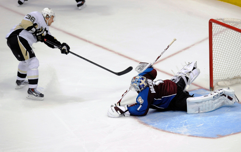 . Pittsburgh Penguins left wing Jussi Jokinen, left, of Finland, scores against Colorado Avalanche goalie Semyon Varlamov, right, of Russia, in the shootout of an NHL hockey game Sunday, April 6, 2014, in Denver. The Penguins won 3-2. (AP Photo/Chris Schneider)