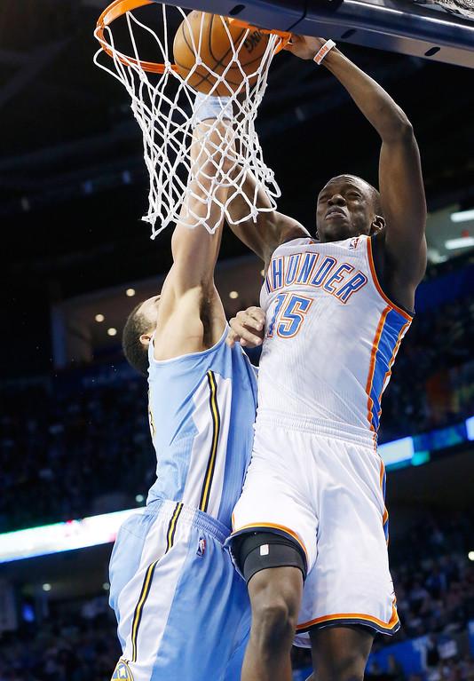 . Oklahoma City Thunder guard Reggie Jackson (15) dunks on Denver Nuggets center JaVale McGee (34) in the third quarter of an NBA basketball game in Oklahoma City, Tuesday, March 19, 2013. Denver won 114-104. (AP Photo/Sue Ogrocki)