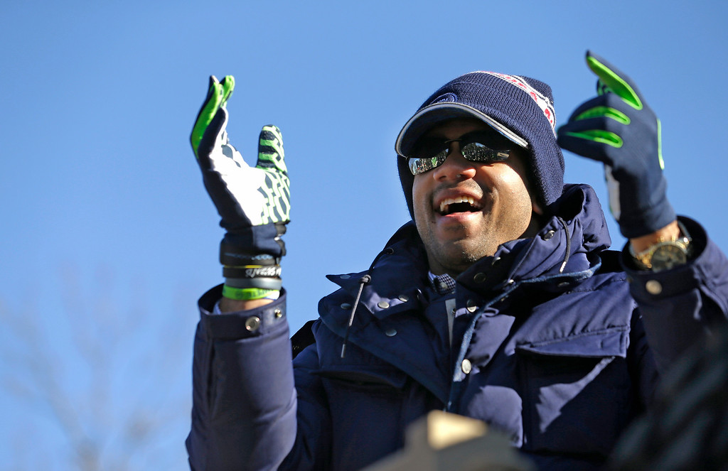 . Seattle Seahawks quarterback Russell Wilson applauds fans during a parade for the NFL football Super Bowl champions Wednesday, Feb. 5, 2014, in Seattle. (AP Photo/Elaine Thompson)