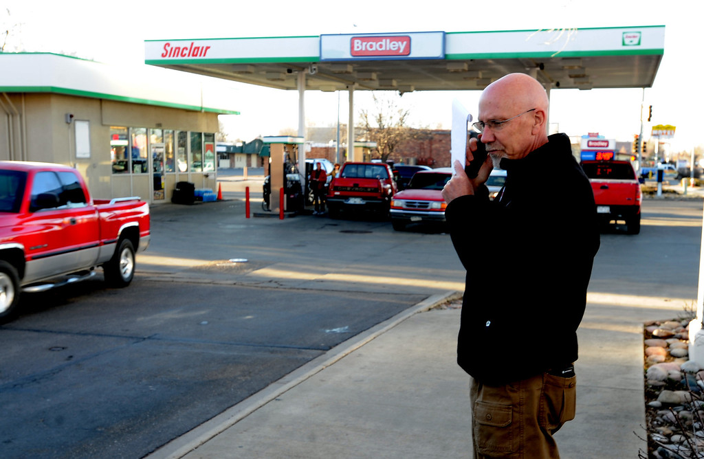 . Longmont Det. Joel Post talks on the phone outside the Bradley Sinclair station where a carjacking and police chase began Wednesday, March 12, 2014, in Longmont, Colo. A man suspected of stealing an SUV in Colorado with a 4-year-old child inside and then carjacking two other vehicles is under arrest.  (AP Photo/The Daily Camera, Cliff Grassmick)