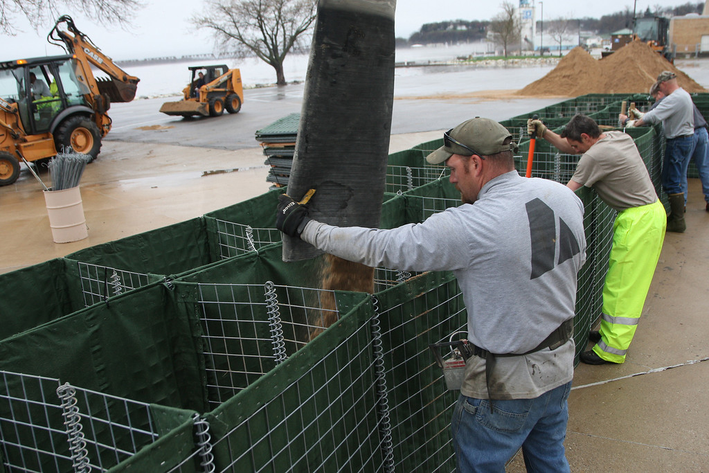 . Dave Newton, with Jazz Concrete Pumping, guides the boom filling sand into the Hesco Barriers surrounding the Memorial Auditorium while city workers compact the sand Thursday April 18, 2013 in Burlington, Iowa.(AP Photo/The Hawk Eye, John Gaines)