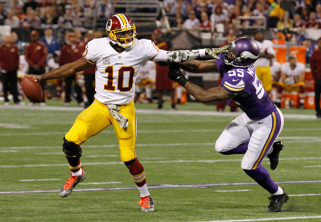 . Washington Redskins quarterback Robert Griffin III, left, tries to break away from Minnesota Vikings outside linebacker Marvin Mitchell during the first half of an NFL football game Thursday, Nov. 7, 2013, in Minneapolis. (AP Photo/Ann Heisenfelt)