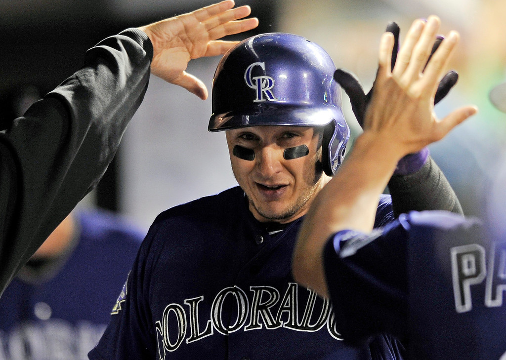 . Colorado Rockies\' Troy Tulowitzki is congratulated int he dugout by teammates after scoring on an RBI single by Wilin Rosario  during the fourth inning of a baseball game against the San Francisco Giants on Tuesday, Aug. 27, 2013, in Denver. (AP Photo/Jack Dempsey)
