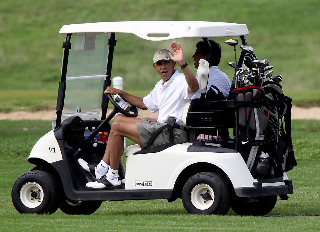 . President Barack Obama waves from the first fairway at Mid-Pacific County club with friend Mike Ramos during his holiday vacation in Kaneohe, Hawaii, Tuesday, Dec. 28, 2010.  (AP Photo/Chris Carlson)