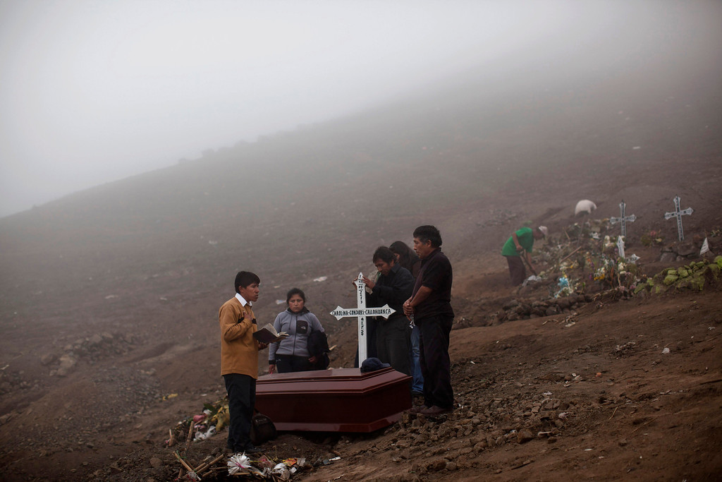 . In this July 19, 2013 photo, a pastor, left, leads a prayer during Maira Condori\'s burial at the Virgen de Lourdes cemetery in Lima, Peru. For roughly four months a year, the sun abandons Peru\'s seaside desert capital, suffocating it under a ponderous gray cloudbank and fog that coats the city with nighttime drizzles. Limenos don scarfs and jackets and complain of slipping into a gloom of seasonal depression. (AP Photo/Rodrigo Abd)