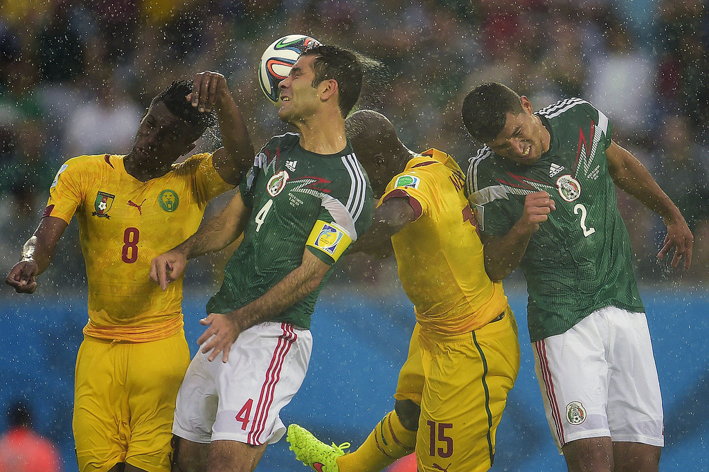 . Cameroon\'s forward Benjamin Moukandjo and Cameroon\'s forward Pierre Achille Webo (3L) fight for the ball with Mexico\'s defender and captain Rafael Marquez and Mexico\'s defender Francisco Rodriguez (R) during a Group A football match between Mexico and Cameroon at the Dunas Arena in Natal during the 2014 FIFA World Cup on June 13, 2014. PIERRE-PHILIPPE MARCOU/AFP/Getty Images