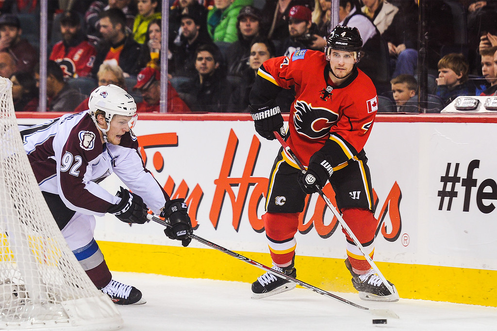 . CALGARY, AB - DECEMBER 6: Kris Russell #4 of the Calgary Flames skates with the puck against Gabriel Landeskog #92 of the Colorado Avalanche during an NHL game at Scotiabank Saddledome on December 6, 2013 in Calgary, Alberta, Canada. (Photo by Derek Leung/Getty Images)