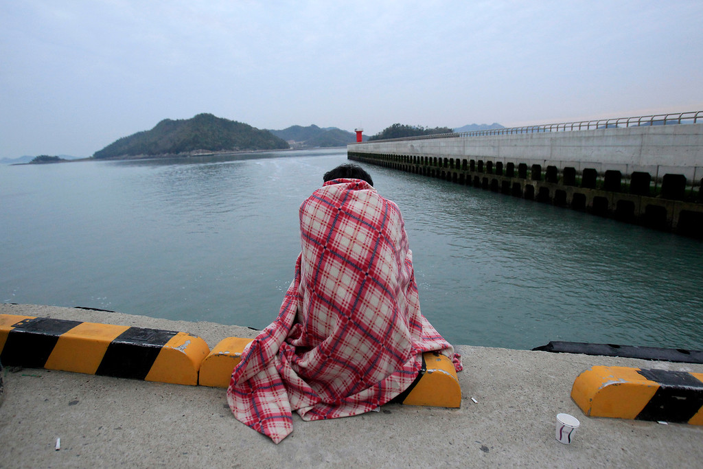 . A relative waits for their missing loved one at a port in Jindo, South Korea, Wednesday, April 16, 2014. A ferry carrying 459 people, mostly high school students on an overnight trip to a tourist island, sank off South Korea\'s southern coast on Wednesday, leaving nearly 300 people missing despite a frantic, hours-long rescue by dozens of ships and helicopters. (AP Photo/Ahn Young-joon)