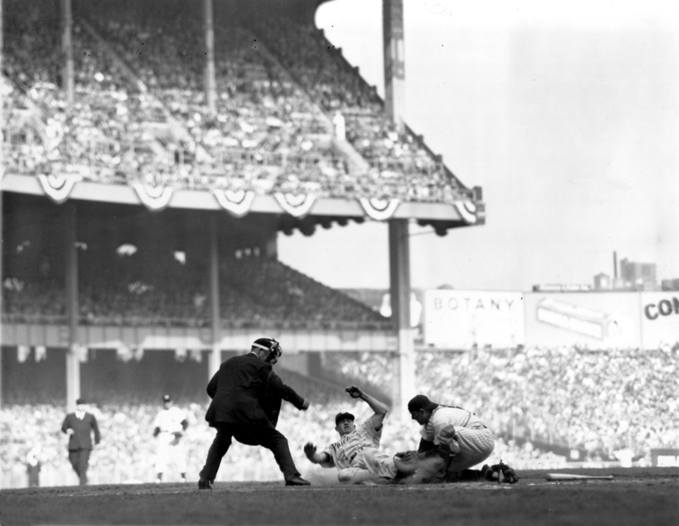. New York Yankees catcher Yogi Berra tags the sliding Philadelphia Phillies shortstop Granny Hamner for an out at home plate and second half of double play in 4th inning in the fourth and final World Series game at Yankee Stadium in New York City, Oct. 7, 1950.  Yankees won, 5-2, to retain World Series Championship, four games to none.  Umpire is Charley Berry.  (AP Photo)