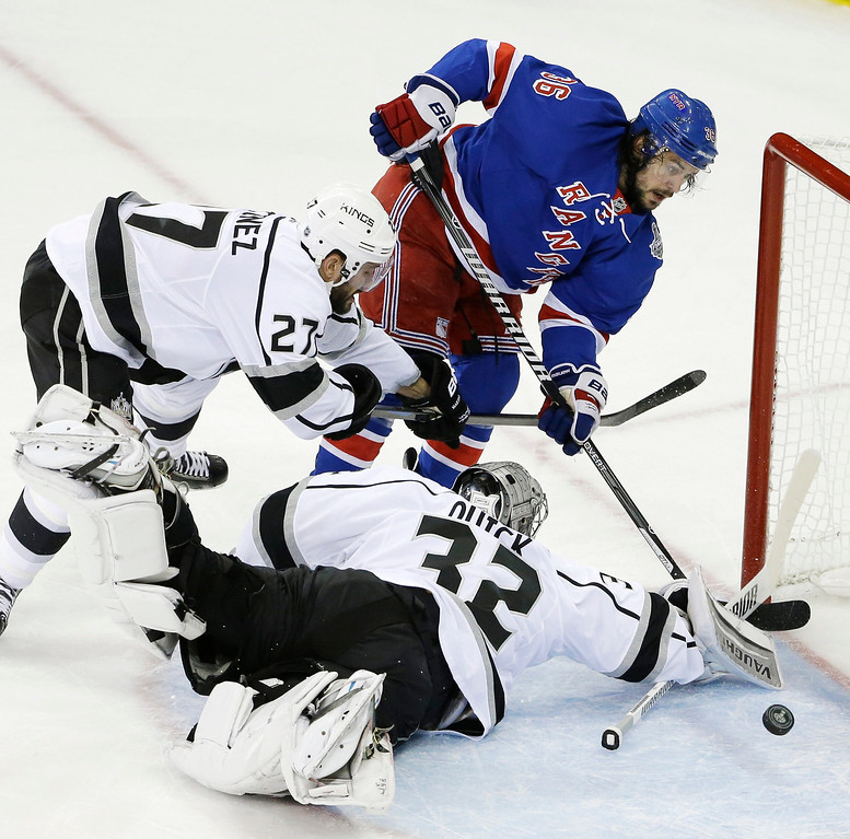 . Los Angeles Kings goalie Jonathan Quick (32) blocks a shot on goal by New York Rangers right wing Mats Zuccarello (36) as Los Angeles Kings defenseman Alec Martinez (27) helps defend in the first period during Game 3 of the NHL hockey Stanley Cup Final, Monday, June 9, 2014, in New York. (AP Photo/Frank Franklin II)