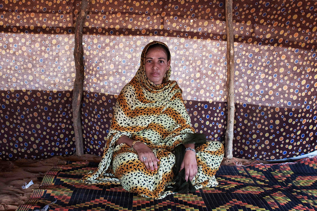 . Zeinab Mint Mohamed, 22, poses for a picture in her home in Mbera refugee camp, Mauritania, May 24, 2012. Mint Mohamed, along with her sisters and 2-month old boy Habibi, fled her hometown of Nara, Mali, in March and took two days in Mbera to settle just outside the official camp grounds. Mbera, a refugee camp set up for people fleeing violence in northern Mali, is home to more than 64,000 people, according to the United Nations\' refugee agency, UNHCR. While most live in UNHCR-donated tents, hundreds of families living outside the official camp grounds reside in informal structures built by whatever materials they can find, including sticks, blankets, towels and empty cement bags. Picture taken May 24, 2012. REUTERS/Joe Penney