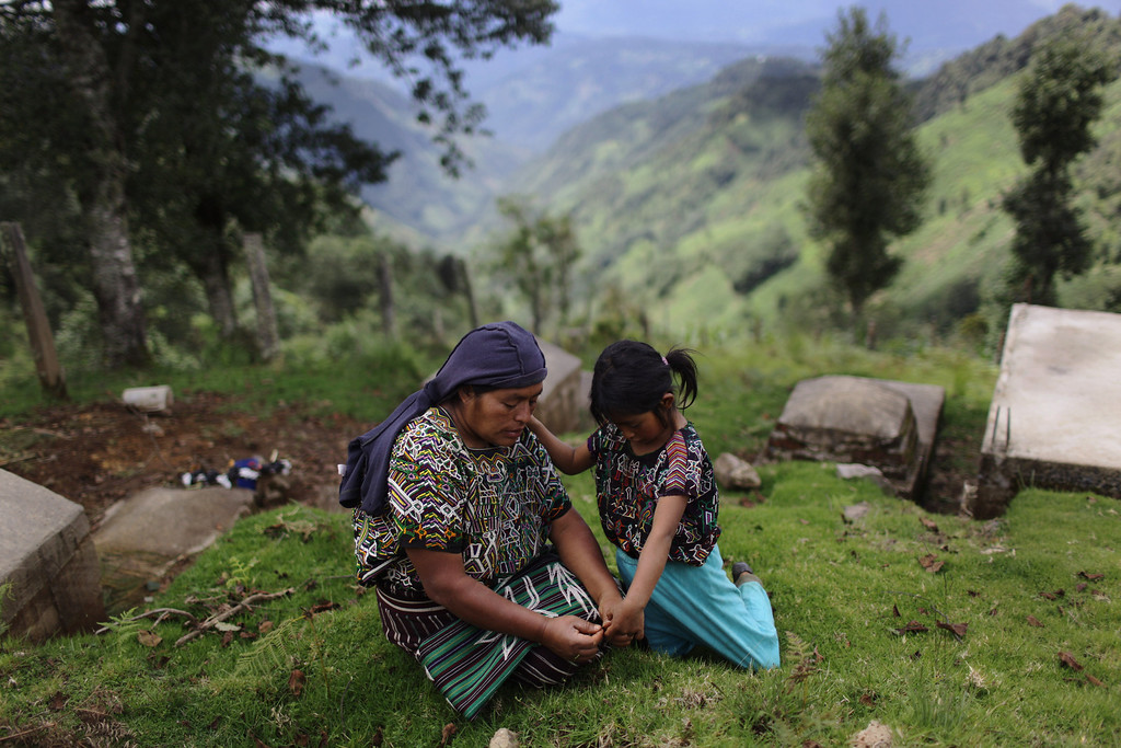 ". In this photo taken July 23, 2011, Juana Matom rests with her daughter at the Vijolom II cemetery in Nebaj, Guatemala. Guatemalan soldiers allegedly killed Matom\'s brother and father in Sept. 1982 during a raid on the community of Vivitz in Nebaj municipality. Twenty-nine years later, in June 2011, the Public Ministry brought charges against Gen. Hector Mario Lopez Fuentes in connection with the planning and ordering of bloody military operations that were part of the military plan coined ""Victoria 82,\"" among other crimes during his time as the Defense Ministry\'s Chief of Staff, including the extermination of residents in villages within the municipality of Nebaj during the government of Efrain Rios Montt (1982-1983). (AP Photo/Rodrigo Abd)"